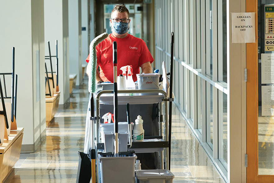 [photo of Drew Davies pushing a cleaning cart]