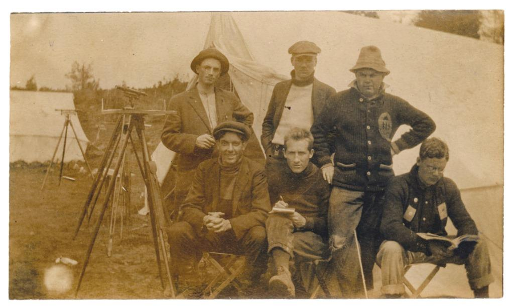 [1914 photo of members of 5th Field Company, one wearing a Queen's sweater, at a surveying field camp in Barriefield]