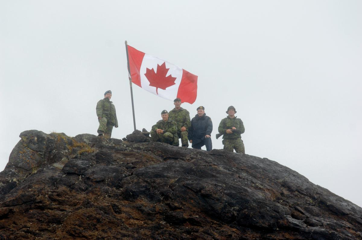 [2007 photo of Whitecross and colleagues standing on a rocky area in Iqualuit on a joint training mission.]