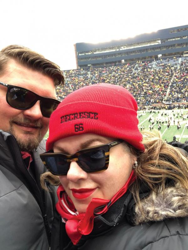 [photo of Kate Kemplin and her husband Ben at a football game]