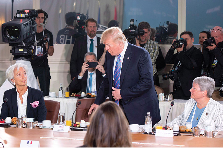 [photo of Donald Trump entering the G7 summit breakfast while Christine Lagarde (IMF) and Lt.-Gen. Christine Whitecross look on.
