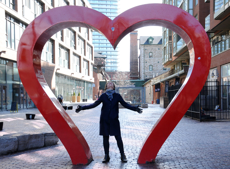 [photo of Janet Fanaki standing under a giant heart-shaped sculpture]