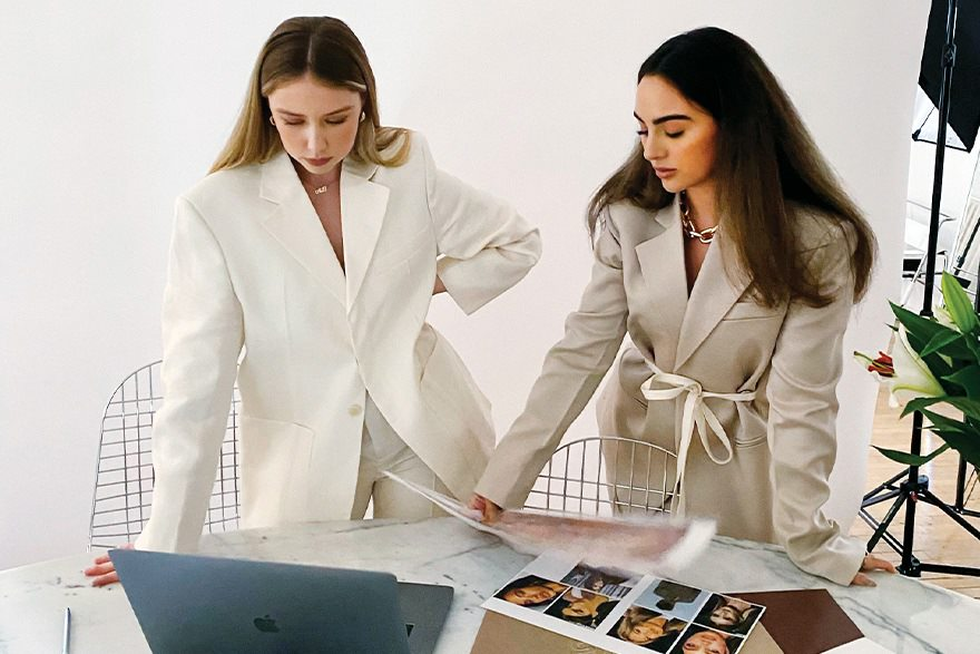Adrien Bettio and Hyla Nayeri stand at a desk wearing elegant business suits.