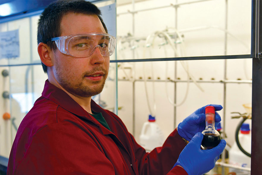 [photo of Alex Veinot in a chemistry lab.]