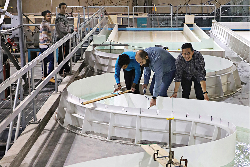 [photo of graduate students conducting research at the meandering channel in the Queen's Coastal Engineering Lab]