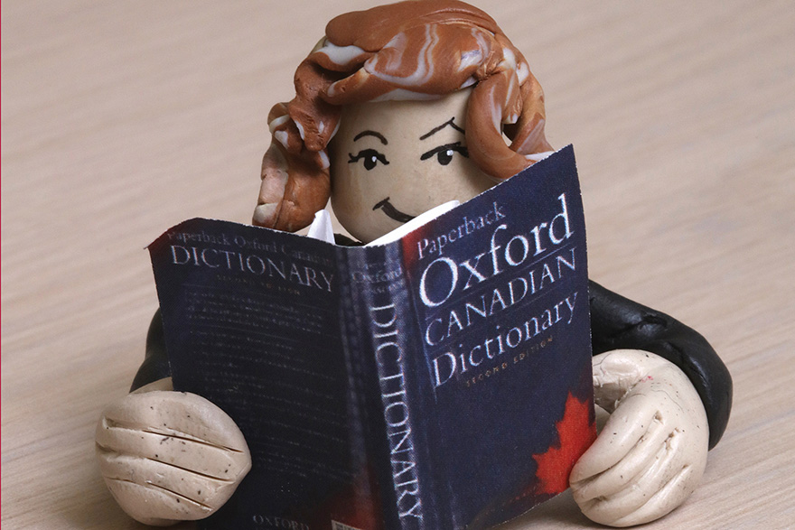 [photo of a miniature figure reading a dictionary]