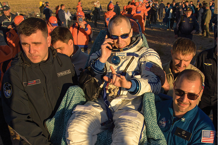 [photo of Drew Feustel being carried to a medical tent after landing in Kazakhstan]