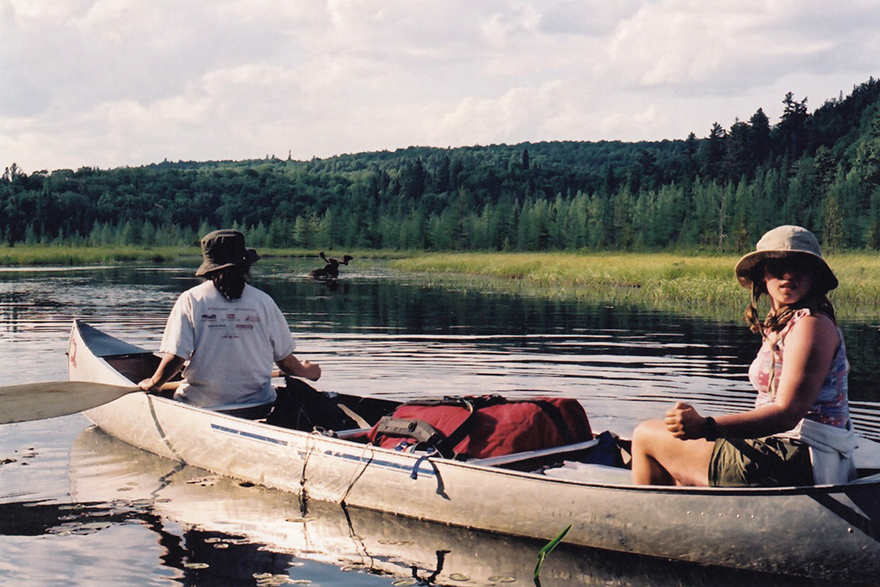[photo of Camp Outlook campers canoeing on a lake. A moose is in the background]