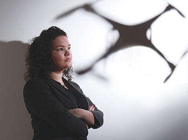 [photo of Ciara Bracken-Roche with a shadow of a drone behind her]