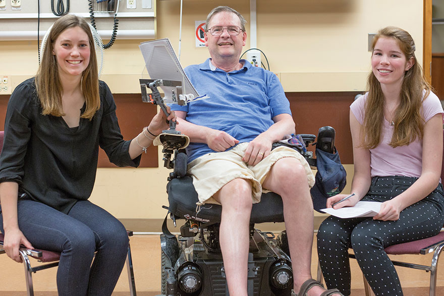 [photo of students Leigh Janssen and Olivia Roud with Kingston resident Jim Stinson]