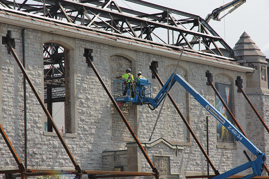 [Workers are tearing out stone that has filled these window frames since 1970. New heritage-style glass windows will be installed by December.]