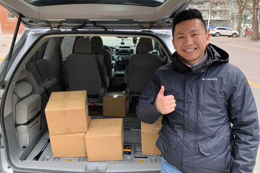 [photo of medical student standing by a car filled with boxes of medical supplies]