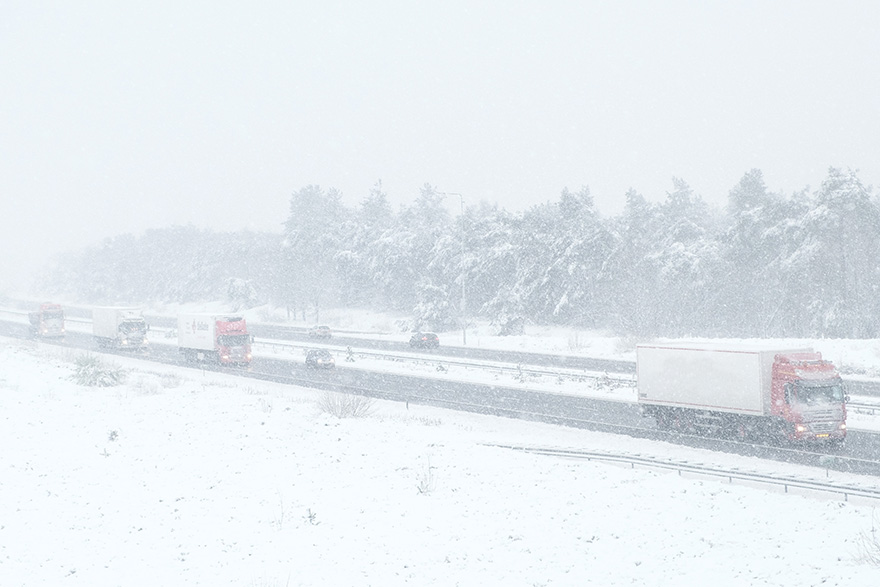 [stock photo of trucks driving on highway in winter]