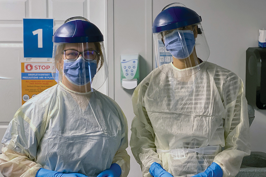 [photo of two masked and gowned doctors at the Markham COVID-19 Assessment Centre]