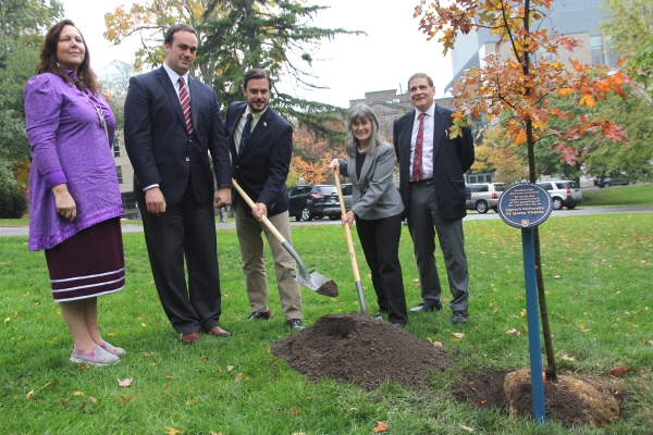 [Dignitaries help plant tree]