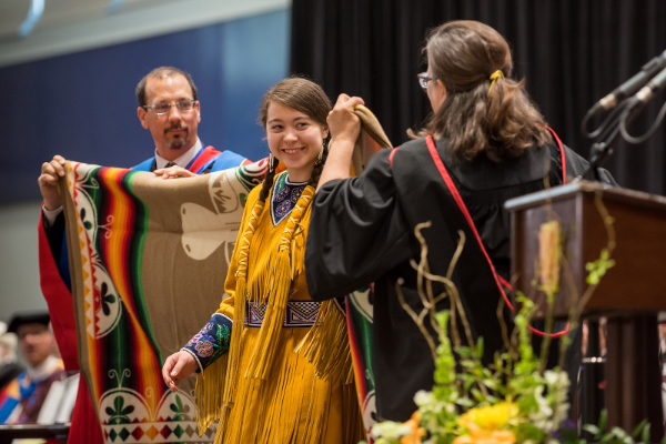 A graduate of the Engineering and Applied Science class being presented with a Pendleton blanket. (Queen's University/Garrett Elliott)