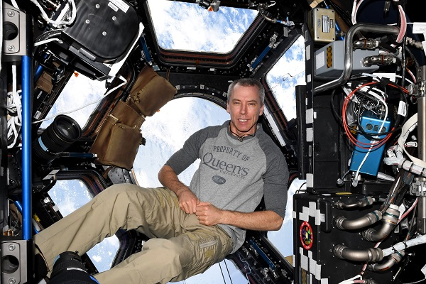 [Dr. Feustel floats above the Earth (Photo: University Relations)]