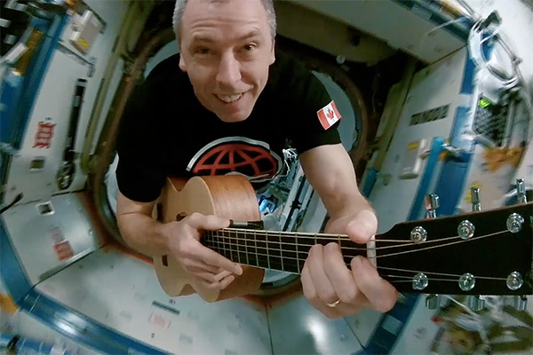 Astronaut Drew Feustel playing a guitar while floating through the International Space Station.