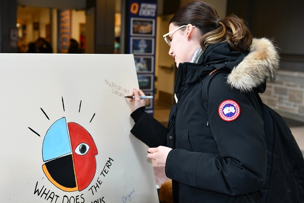 A student contributes to the Indigenous Awareness Week whiteboard. (University Communications)