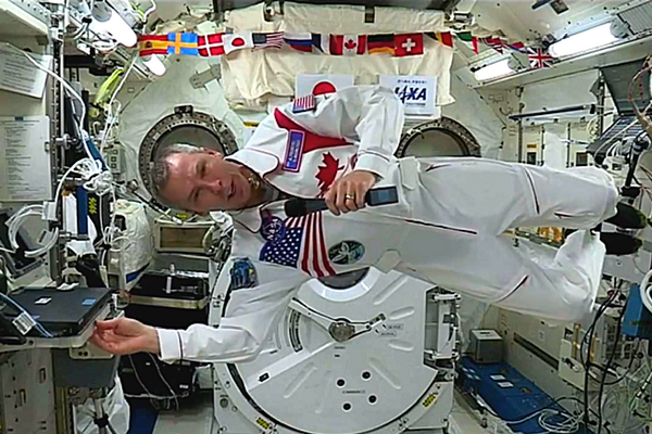 [Dr. Feustel broadcasts in International Space Station (Photo: Queen's/Facebook Live)]