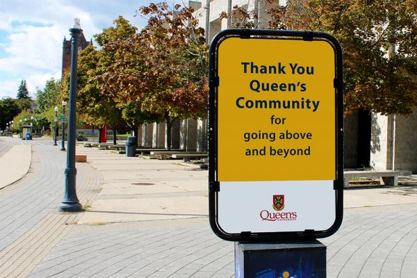 On-campus sidewalk signage thanking the Queen's community for going above and beyond.