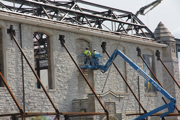 Workers are tearing out stone which has sat in these window frames since 1970. In its place will be heritage-style glass windows, which will be installed by December.