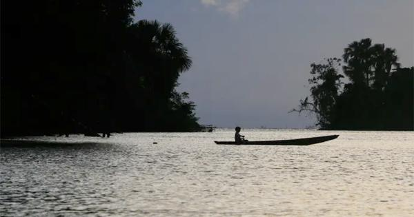 A Brazilian boy in a dugout canoe crosses a river in the evening.