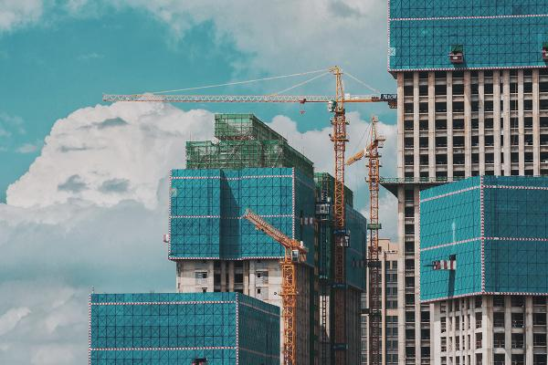 Cranes work to build large buildings