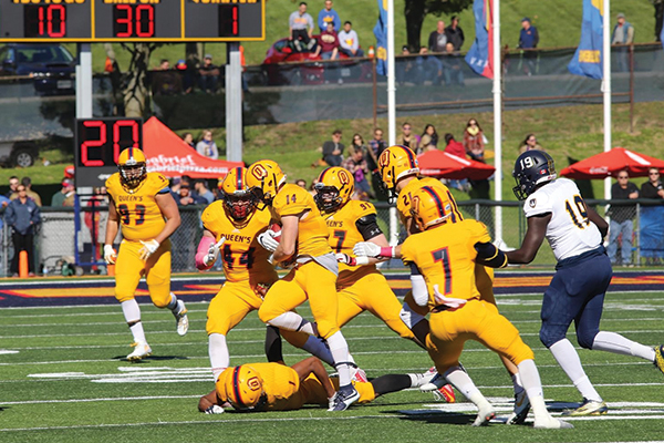 """Queen's Gaels football players grab a turnover again the Laurier Hawks"""