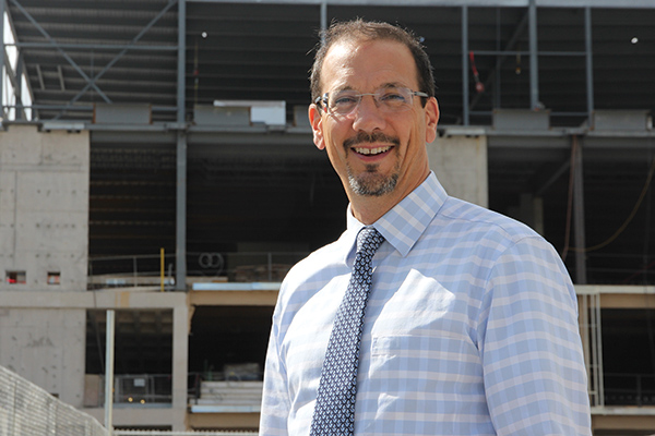 """Dean of the Faculty of Engineering and Applied Science Kevin Deluzio stands outside the construction site for the Innovation and Wellness Centre"""
