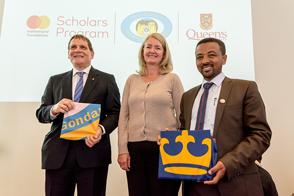 """Queen's Principal Daniel Woolf, Kim Kerr, Deputy Director, Education and Learning, Mastercard Foundation and Asrat Atsedewoyin, Vice-President Academic, University of Gondar exchange university flags to mark the partnership."""