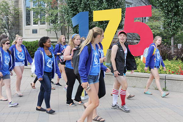 An Orientation group walks past the 175 anniversary numbers on campus.