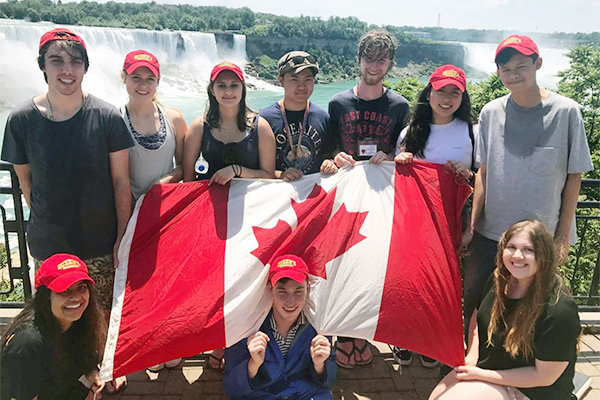 """Australian students participating in Queen's Political Studies Summer Institute hold a Canadian flag as they stand in front of Niagara Falls"""