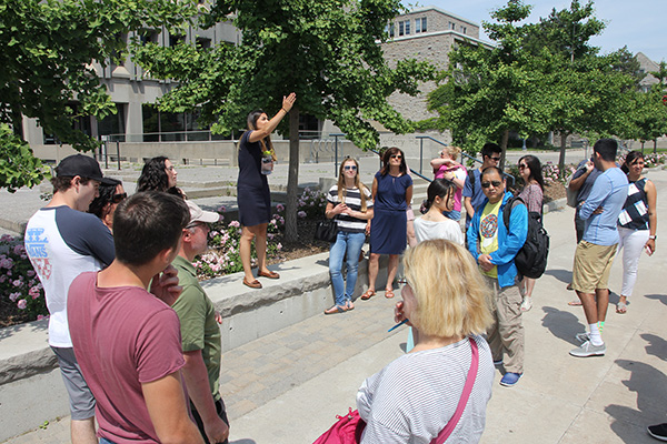 """Students and their families listen to a guide during a campus tour as part of Summer Orientation to Academics and Resources"""