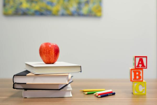 teacher's desk with an apple, books and letter blocks