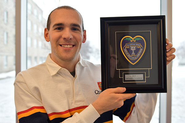 [Wesley Forget holds up the purple heart he received for winning the Ontario Curling Championship.]