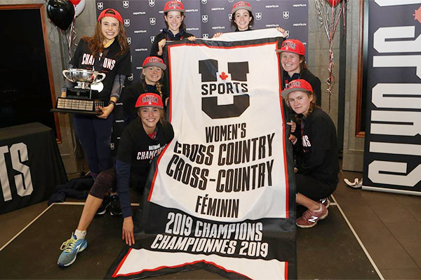 [Gaels hold up the USPORTS women's cross country banner]
