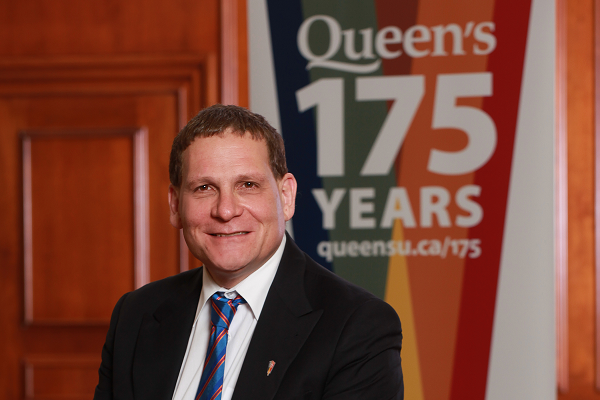 Principal Daniel Woolf with the Queen's 175th banner