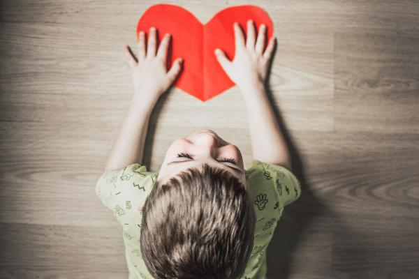 Child holding red paper shaped as a heart (Photo by Anna Kolosyuk, Unsplash)