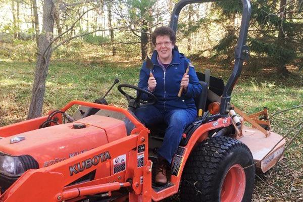 Classics professor Barbara Reeves holds excavating tools as she sits on an orange Kubota tractor.