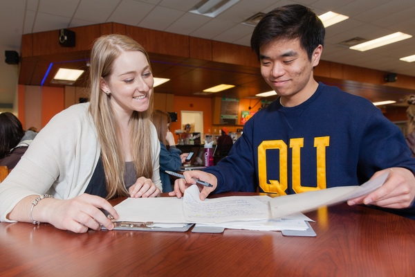 Two students talking at a table.