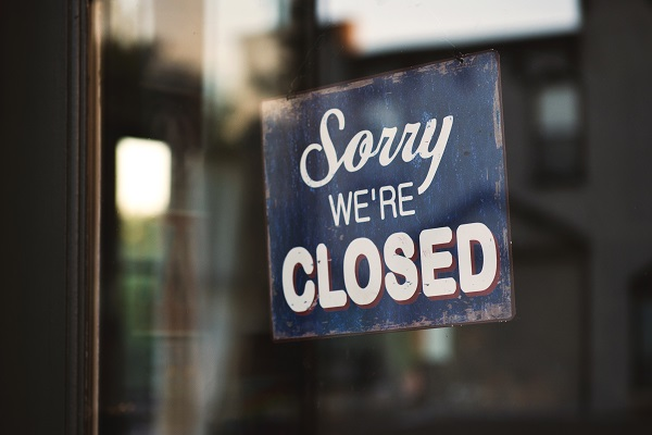 "[Photo of a ""Sorry We're Closed"" sign by Tim Mossholder for Unsplash]"