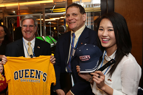 Principal Daniel Woolf hands out some Queen's gear to Steven Simkovits (MBA'97) and Andrea So (Artsci'14) during an alumni event held in Hong Kong.