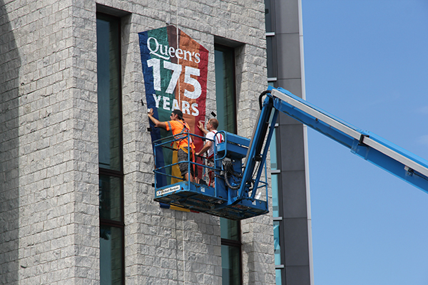 A crew from Jet Signs installs a banner celebrating the 175th anniversary of Queen's University on Stauffer Library.