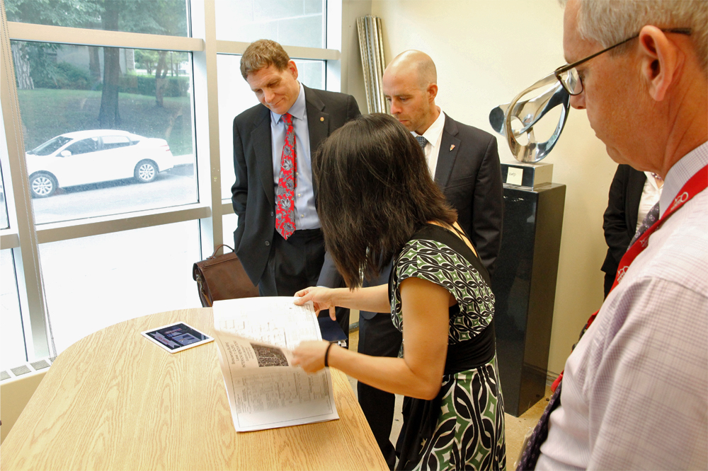 Clarrie Lam, Manager, Facilities and Operations, Queen's CardioPulmonary Unit, shows Principal Daniel Woolf and Provost Benoit-Antoine Bacon the floor plan and architectural renderings of the facility.