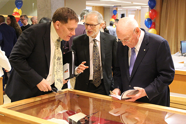 Principal Daniel Woolf, left, and Seymour Schulich, right, look at one of the displays at the newly-opened Schulich-Woolf Rare Book Collection with Alvan Bregman, Head, W.D. Jordan Rare Books and Special Collections. (University Communications)