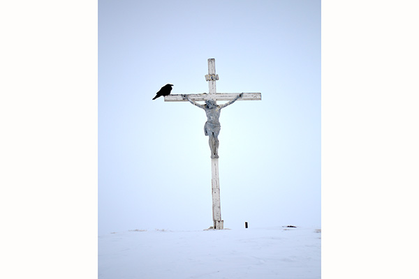 First Prize -Tulugak on the Crucifix - Pond Inlet, Nunavut, Norman Vorano (Art History & Art Conservation): Dr. Vorano was conducting historical research with Inuit elders in Nunavut in 2016. After one session, he stepped outside. The white sky was indistinguishable from the ground. He walked past a towering crucifix erected behind the Catholic Church, on an imposing hill overlooking the community. A raven flew down from the ethereal sky, perched on the Crucifix, and began vocalizing.