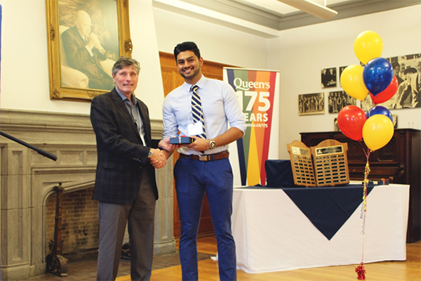 Chintan Dave (Meds'17) accepts the Brian Yealland Community Leadership Award from former Queen's chaplain Brian Yealland. (Photo by Laura Wyatt)