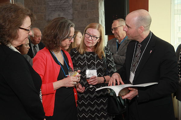 Provost Benoit-Antoine Bacon leafs through a book with, from left, Martha Whitehead, Vice-Provost and University Librarian, Alicia Boutilier, Curator of Canadian Historical Art, and Jan Allen, Director of the Agnes Etherington Art Centre.