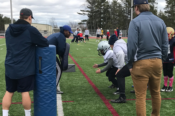 A youth football player learns how to approach a tackle safely to minimize injury risk, during on-field CESAP training. Allen Champagne (MSc'17) (in the white hoodie) offers technique coaching as the player prepares to go through the drill.